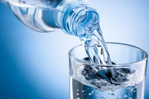 21036145 - pouring water from bottle into glass on blue background